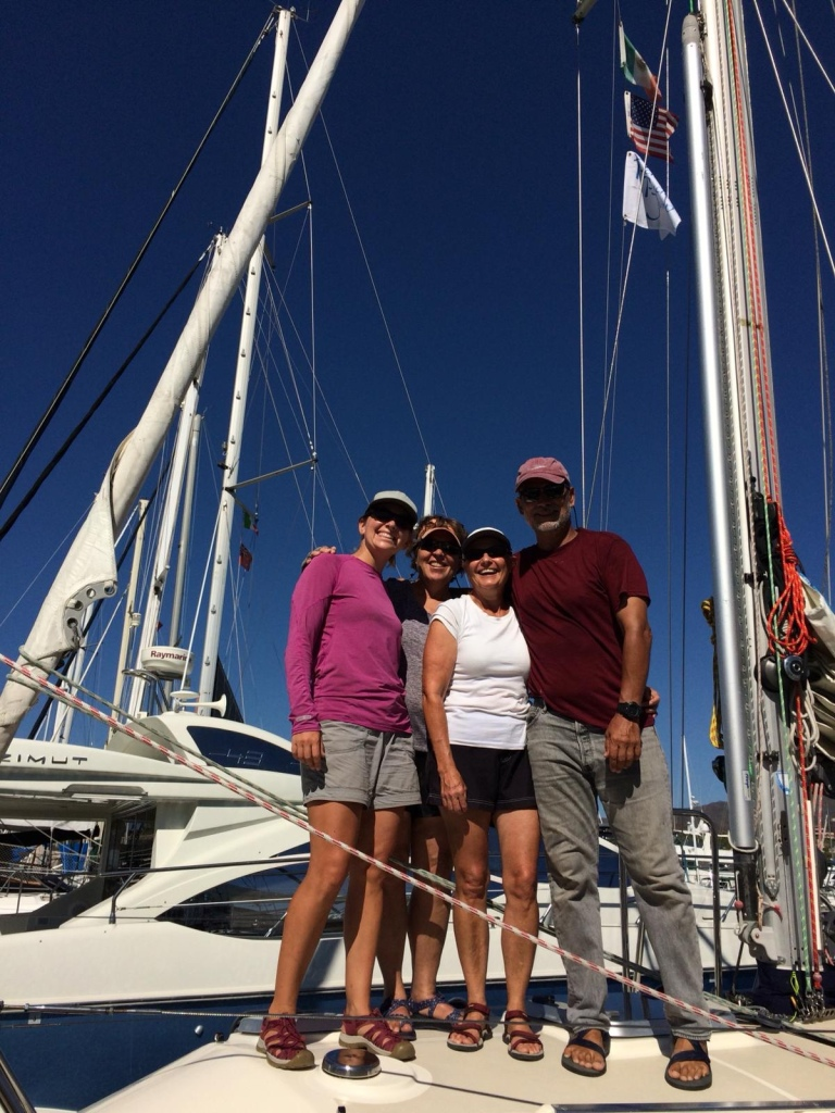 Four crew members are all smiles, arm in arm, on the SV Rapture foredeck, ready to cross the Pacific.